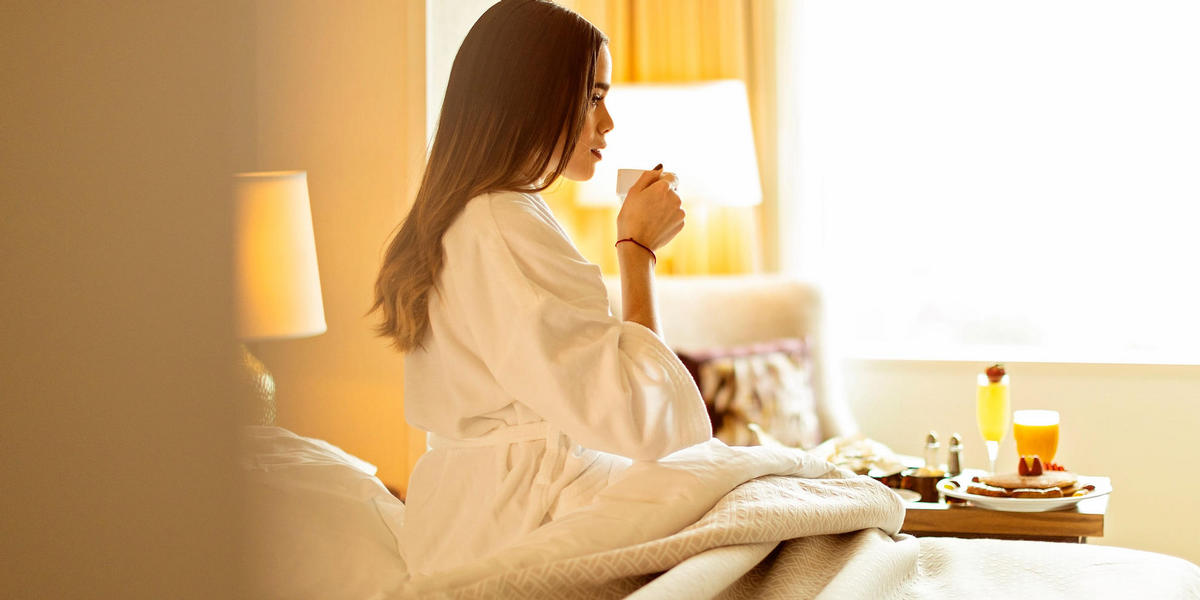 Girl sipping cup of coffee in her robe in hotel room