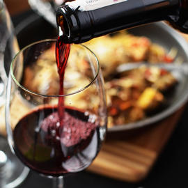 bottle pouring red wine into glass in front of plate of food
