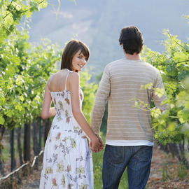 man and woman holding hands in vineyard