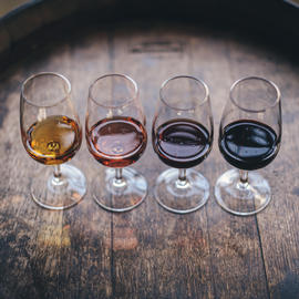 four glasses of wine lined up on a wine barrel