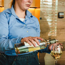 server pouring white wine into wine glass